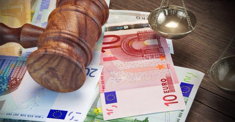 Obrázok euro bankoviek v hodnote niekoľko sto eur, na ktorých je položené sudcovské kladivko. Na obrázku vidno misky váh.